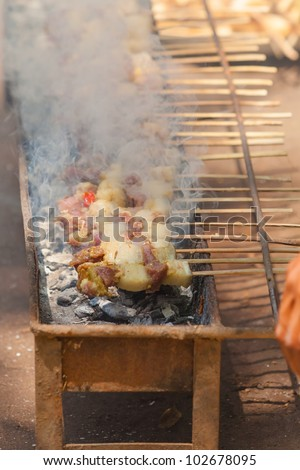 Small barbecue grilling satay skewers on coal