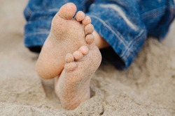 small bare feet of children with small bare toes, soiled with fine sea sand, a child sits on the shores of the Aegean Sea