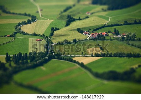 Small Bavarian village in a fields, Germany. Pseudo tilt shift effect - stock photo