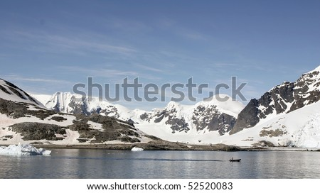 stock-photo-small-bay-in-antrarctic-peninsula-people-on-the-shore-and-rubber-boat-is-passing-by-52520083.jpg