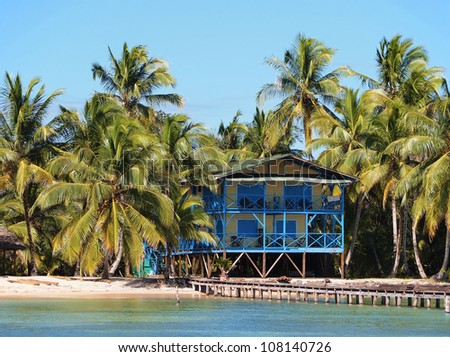 Small beach hotel with coconut trees and a dock, Caribbean, Panama