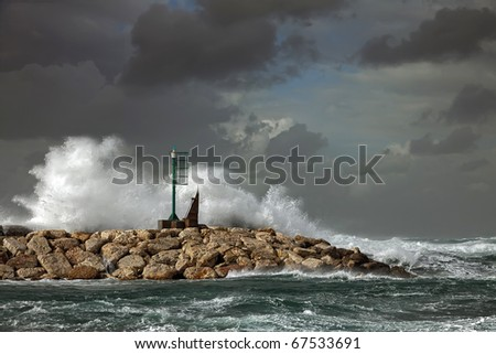 Small beacon on a pier on the storm background