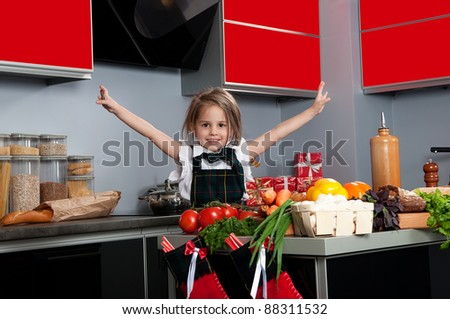 Small beautiful girl, in the form of a cook in the kitchen. Cooking Christmas dinner. - stock photo