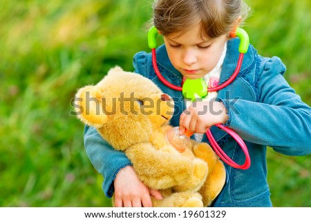 Small beautiful girl listens by means of stethoscope as heart of toy bear cub fights. - stock photo