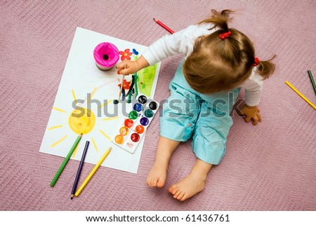 small beautiful girl paints on apaper on floor