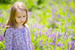 small, beautiful, sad girl alone in a field of purple flowers. child is unwell because of the heat. sunstroke.