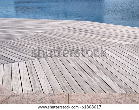 Small beautiful seaside wooden jetty dock pier deck by the ocean