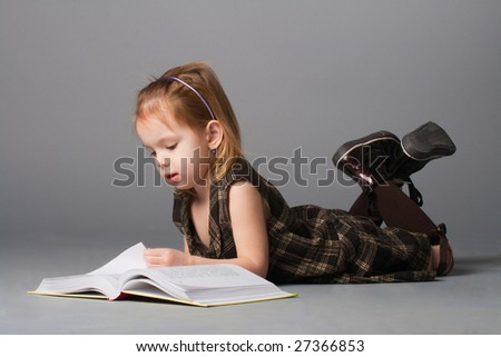 Small beauty girl lying and reading interesting book.