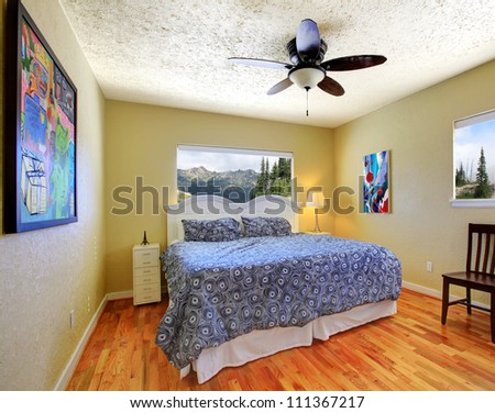 Small bedroom with yellow walls, mountain view and grey and white bed.