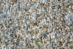 Small beige and grey sea pebbles. Natural stone background or wallpaper picture. Summer holidays and garden design concept. Construction and decoration material. Seaside. Path cover material.