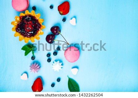 Small berry cake and ripe berries on a blue wooden background. Delicious dessert.Place for your text. #1432262504