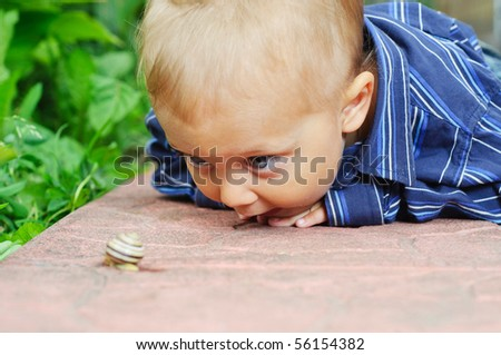 Small biologist. Cute 2-year-old boy found a snail in his garden