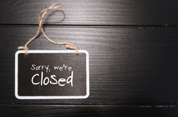 Small black chalkboard sign on black wood background with text handwritten Sorry We're Closed, concept of inform customers shop closing time, or closing or out of business due to bad economy