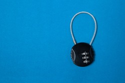 Small black iron cipher lock with a coded set on blue background