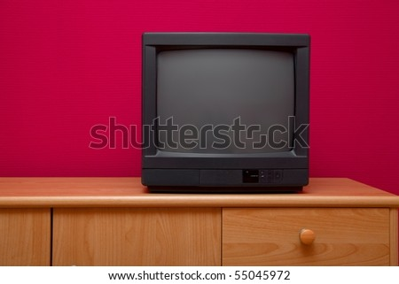 Small black TV on a cabinet