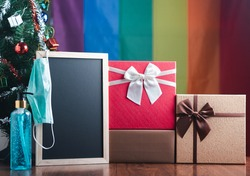 Small blackboard, mask, alcohol gel, and gift boxes on wooden table with a Christmas tree and LGBT flag in the background. Space for text. Concept of Christmas and new year festival.