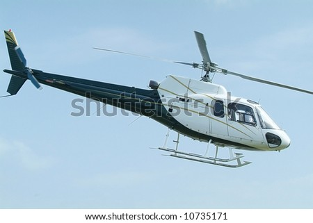 Small, blue and white, passenger helicopter mid-air