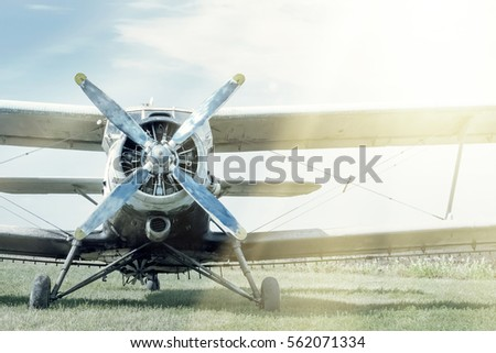 Small blue and white plane on a background of green grass and blue sky. Toned.