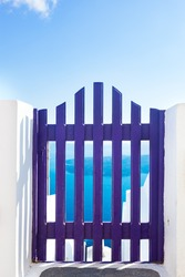 Small blue fence gate in Oia on Santorini island, Greece. Aegean sea and Caldera in the background. Blue sky, travel, vacation time.