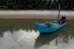 Small blue fishing boat sitting in tidal bay with reflection in water in Pythiu Thailand