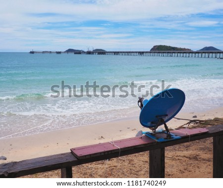 Small blue satellite dish mounted on the wooden​ balcony of the resort​ which​ near the​ sea​ for receive signals from space to amplify the signal to watch television and blue sky with white clouds. #1181740249