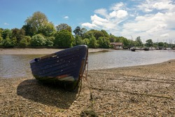 small blue wooden boat rests on riverbed. Weathered old boat