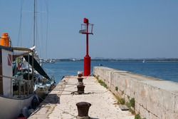 Small boat anchored aside picturesque stone peer with red steel signal post that aids safe navigation trough shallow waters and easy access to Krapanj harbour on a sunny summer day