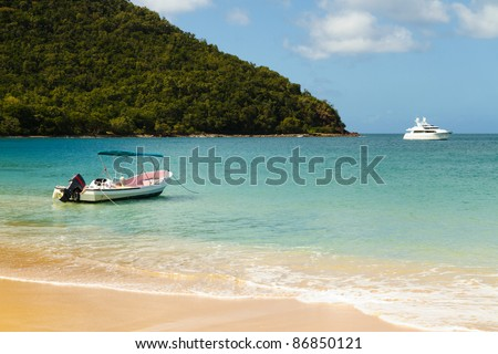 Small boat and yacht floating on the clear waters of the Caribbean