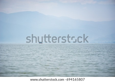 Small boat on a lake in the haze with mountains in the backgroun #694165807
