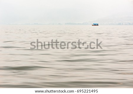 Small boat on a lake in the haze with mountains in the background #695221495