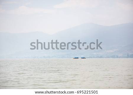 Small boat on a lake in the haze with mountains in the background #695221501