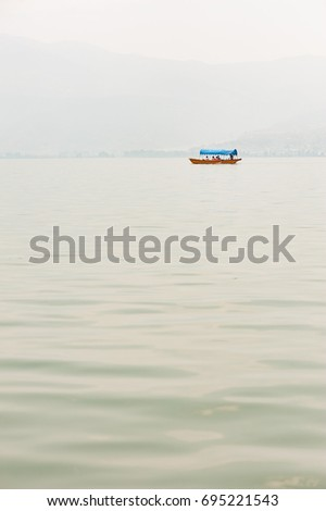 Small boat on a lake in the haze with mountains in the background #695221543