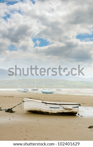 small boat on sandy beach with more boats in background - stock photo