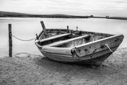 Small boat tied up waiting for the tide