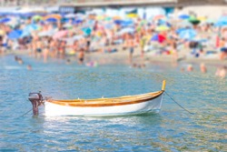 small boat with motor on the water with blurred people on the beach background in hot summer.