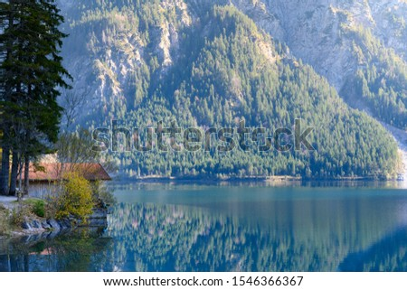 small boathouse at lake plansee in fall season between austrian alps mountains #1546366367