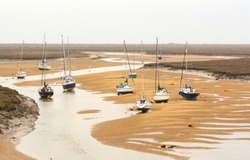 Small boats at low tide at Wells next the Sea, Norfolk, UK
