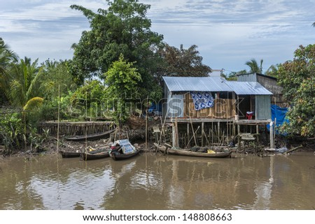 Small boats dock at a shack on stilts in the jungle. As seen in the Vietnam's Mekong Delta: typical dwelling of the people living along the many canals and rivers.  - stock photo