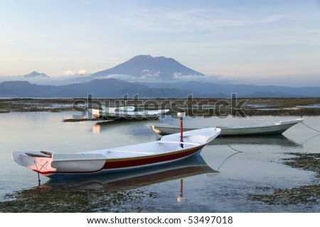 small boats on the reefs of nusa lembongan island indonesia with balis gunung agung , volcano, towering in the background