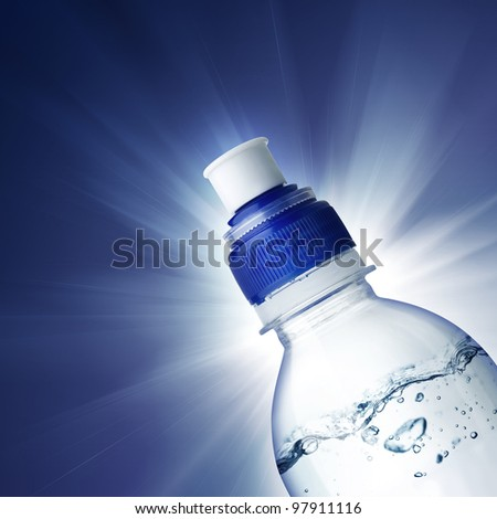 Small bottle of water on blue background with ligth - stock photo