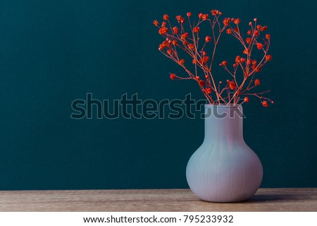 Small Bouquet of Red Flowers in Vintage Vase on Wood Table Blue Navy Wall Background. Styled Stock Image Mockup for Text Artwork Quotes Lettering Website Banner Template. Easter Mother's Day #795233932
