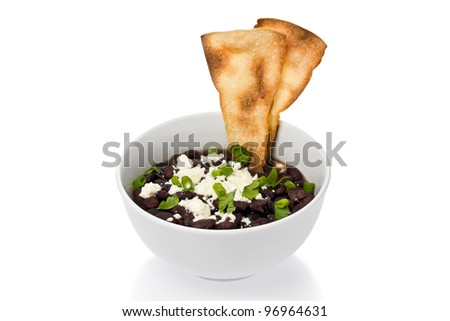 Small bowl of black beans with cheese, and two tortilla chips.