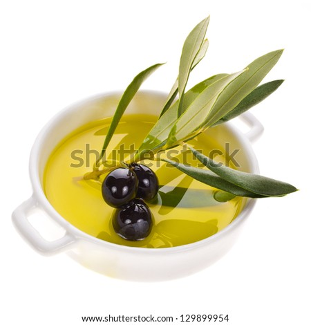 small bowl with olive oil decorated with a small twig with black olives fruit isolated on white background