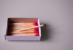 small box containing new matchsticks and a burnt out matchstick