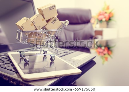 Small boxes in a shopping cart on a smart tablet and a laptop computer in office room. Concept of online shopping that consumer or customer can buy things from retailer stores online via the internet.