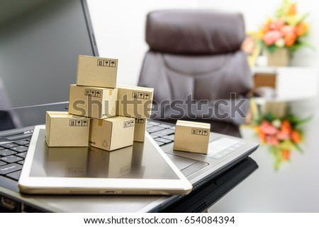 Small boxes on a white smart tablet and a laptop in an office. Concept of electronic shopping that clients can buy, send or receive goods by using the internet. Things can be sold online virtually.