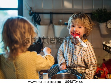 Small boy and girl indoors in kitchen at home, helping with cooking. stock photo