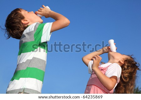 Small boy and the girl against the blue sky, with pleasure drink yoghurt. - stock photo