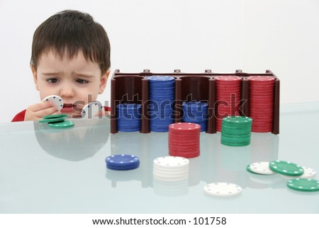 Small boy behind a stack of poker chips.