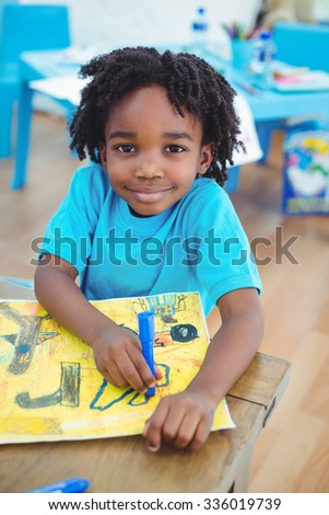 Small boy drawing a picture at their desk